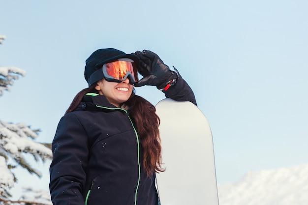 Jeune femme tenant son snowboard et ses lunettes sur une montagne enneigée