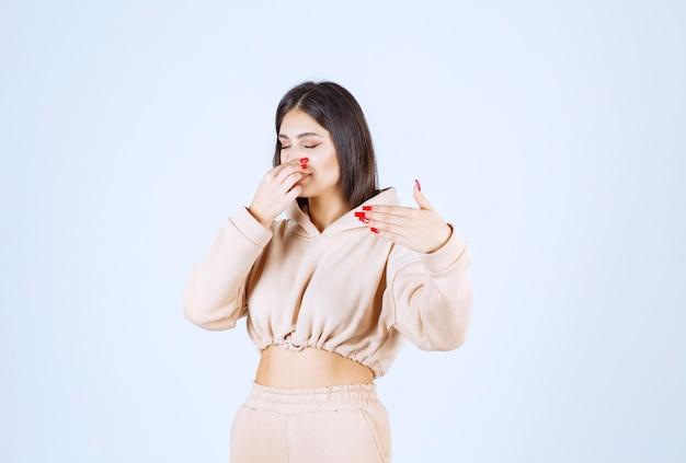 Jeune femme tenant son souffle, ce qui signifie mauvaise odeur