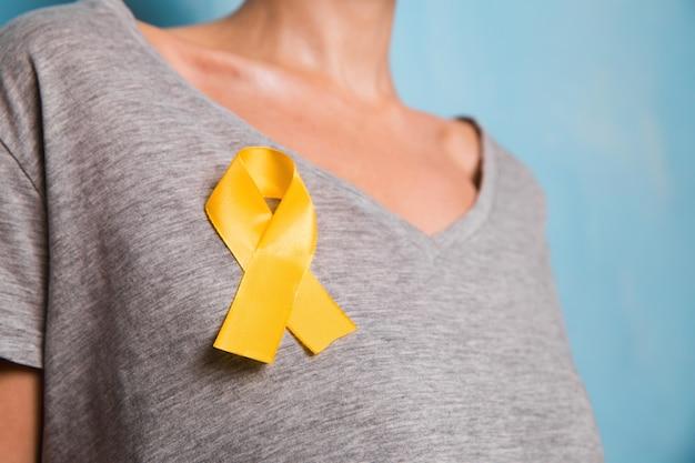 Jeune femme tenant un symbole de sensibilisation au ruban d'or jaune pour l'endométriose, la prévention du suicide, le cancer des os du sarcome, le cancer de la vessie, le cancer du foie et le concept de cancer infantile. soins de santé. fermer.