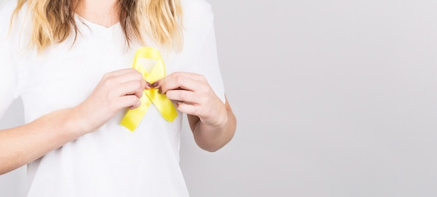 Jeune femme tenant le symbole de sensibilisation du ruban d'or jaune pour l'endométriose, la prévention du suicide, le cancer des os de sarcome, le cancer de la vessie, le cancer du foie et le concept de cancer infantile.