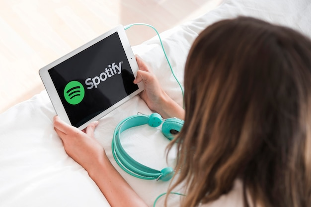 Jeune femme tenant une tablette avec l'application spotify