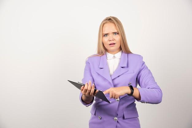 Jeune femme tenant une tablette sur fond blanc. photo de haute qualité