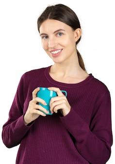 Jeune femme tenant une tasse avec une boisson chaude isolée on white