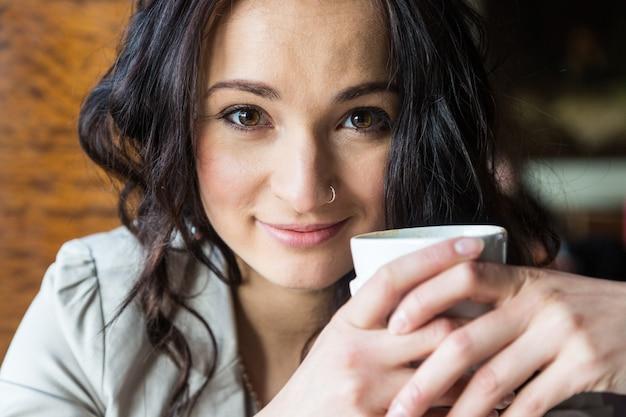 Jeune femme tenant une tasse de boisson chaude