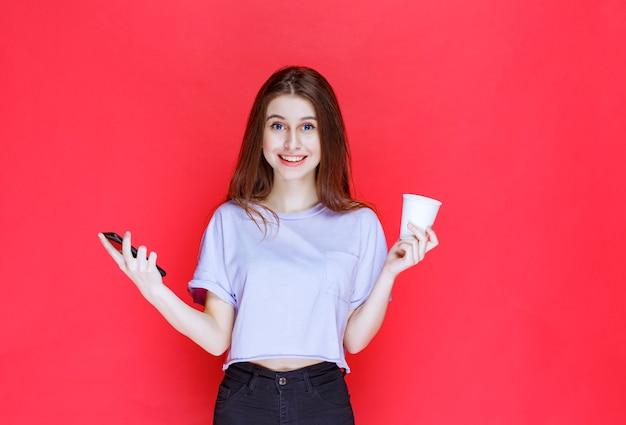Jeune femme tenant une tasse de boisson et un smartphone noir avec un visage souriant.