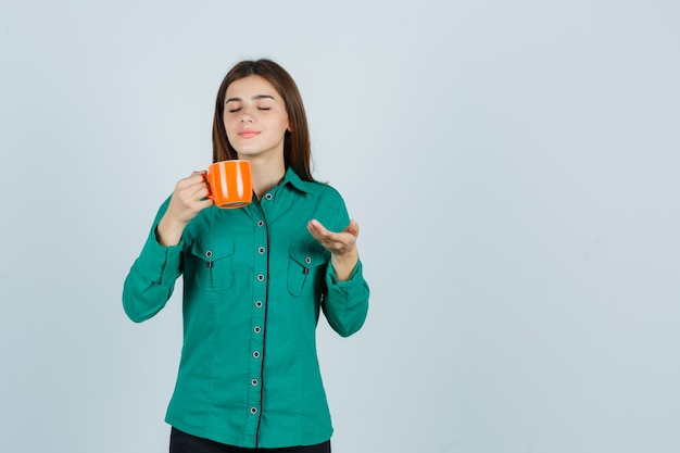 Jeune femme tenant une tasse de thé orange, montrant quelque chose en chemise et à la recherche de calme. vue de face.