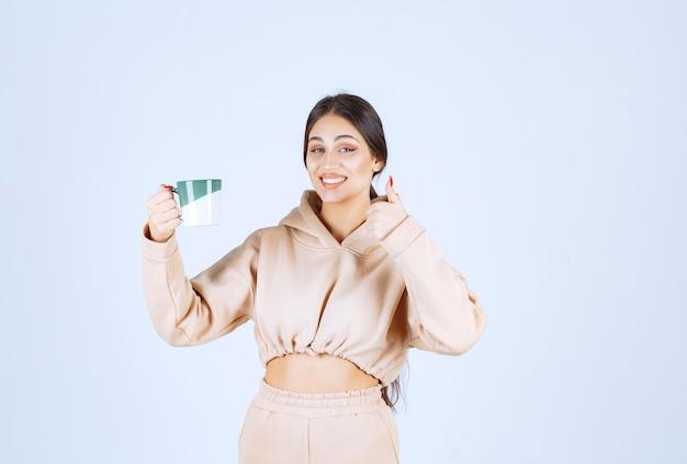 Jeune femme tenant une tasse verte et montrant sa satisfaction