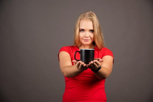 Jeune femme tenant une tasse vide sur un mur noir.