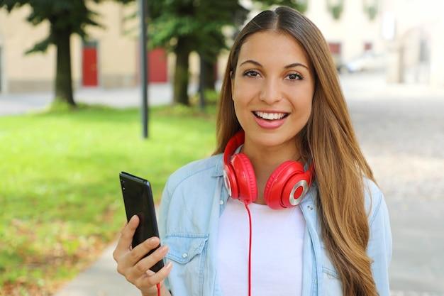 Jeune femme tenant un téléphone intelligent pour choisit la musique avec sa nouvelle application mobile