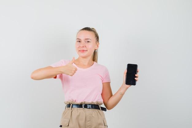 Jeune femme tenant un téléphone mobile, montrant le pouce vers le haut en t-shirt et pantalon et à la bonne humeur