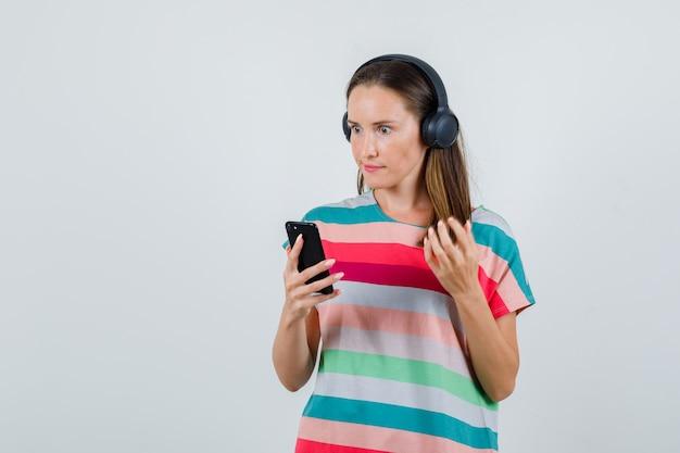 Jeune femme tenant un téléphone mobile en t-shirt, écouteurs et à la colère. vue de face.