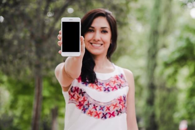 Jeune femme tenant un téléphone portable à la main