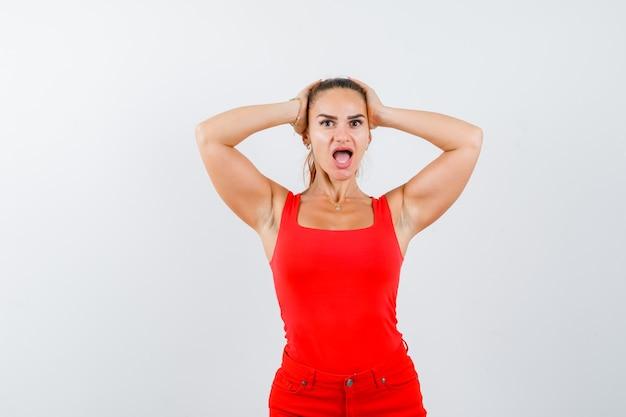 Jeune femme tenant la tête de la main om en maillot rouge, pantalon rouge et à la perplexité. vue de face.