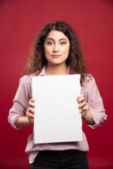 Jeune femme tenant une toile vide.