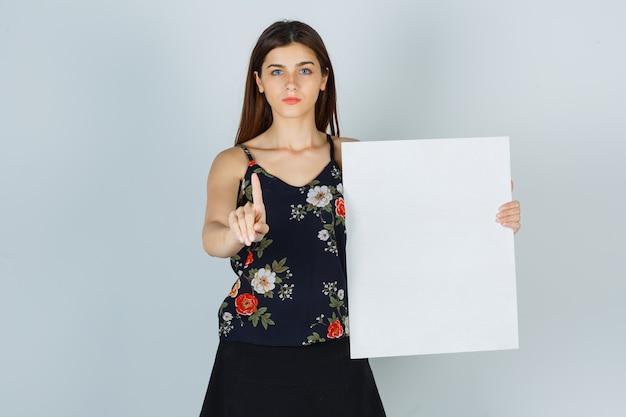 Jeune femme tenant une toile vierge, montrant la prise d'un geste minute en chemisier, jupe et semblant sérieuse, vue de face.