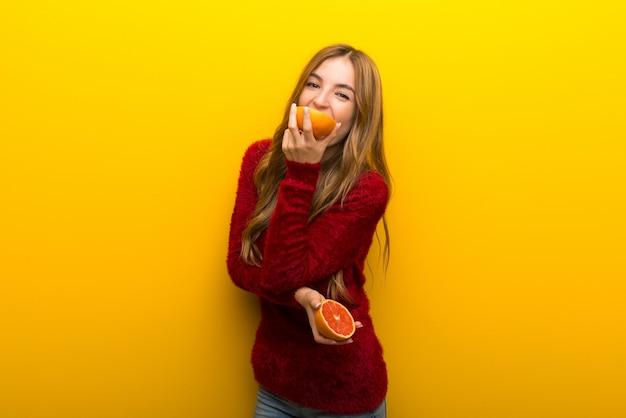 Jeune femme tenant des tranches d'orange sur fond jaune vibrant