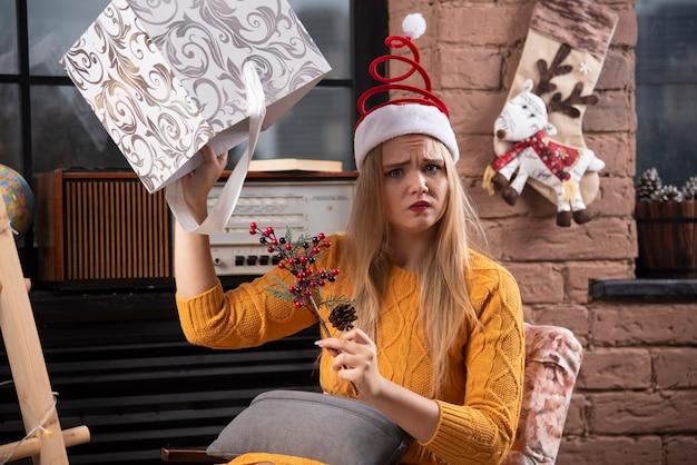 Jeune femme tenant tristement la boîte de noël.