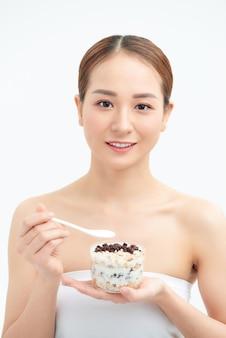 Jeune femme tenant un verre avec du yogourt naturel, de délicieux raisins secs et des céréales le matin. petit-déjeuner, concept de nutrition diététique