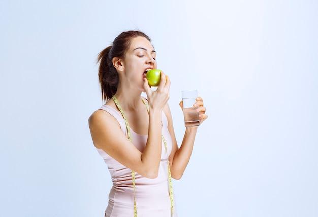 Jeune femme tenant un verre d'eau et mordant une pomme verte
