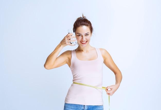 Jeune femme tenant un verre d'eau pure et mesurant son tour de taille
