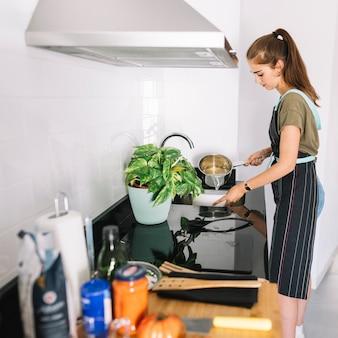 Jeune femme tendant des pâtes bouillies dans une passoire