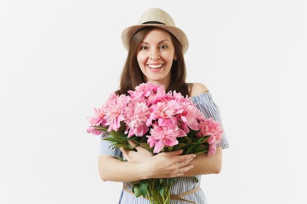 Jeune femme tendre en robe bleue, chapeau tenant un bouquet de belles fleurs de pivoines roses isolées sur fond blanc. saint-valentin, concept de vacances de la journée internationale de la femme. espace publicitaire.