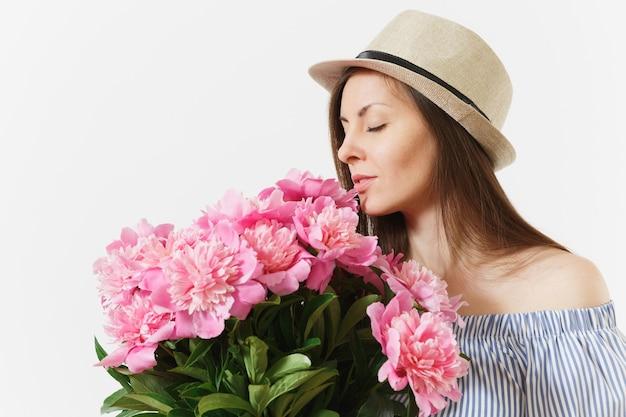 Jeune femme tendre en robe bleue, chapeau tenant, reniflant bouquet de fleurs de pivoines roses isolées sur fond blanc. saint-valentin, concept de vacances de la journée internationale de la femme. espace publicitaire.