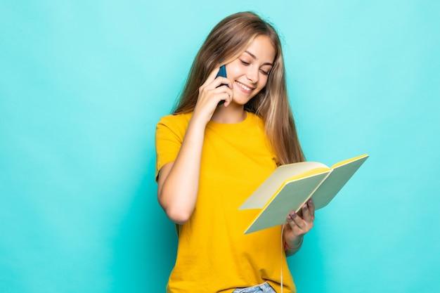Jeune femme tenir planificateur écrire des secrets privés dans le journal mur turquoise isolé