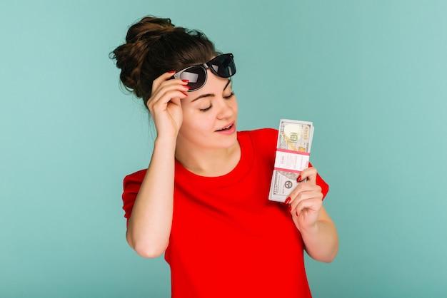 Jeune femme tenir vers une pile d'argent isolé sur fond bleu