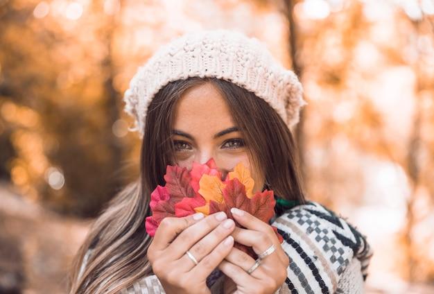Jeune femme, tenue, automne, feuilles, près, face