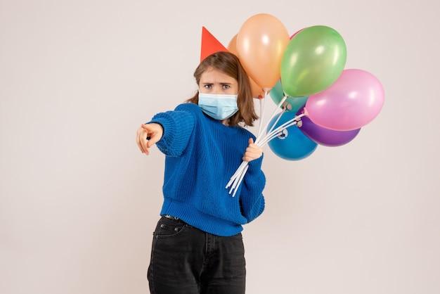 Jeune femme, tenue, ballons colorés, dans, masque, blanc