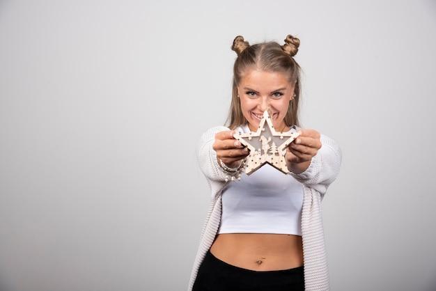 Jeune femme en tenue blanche montrant une étoile sur fond gris.
