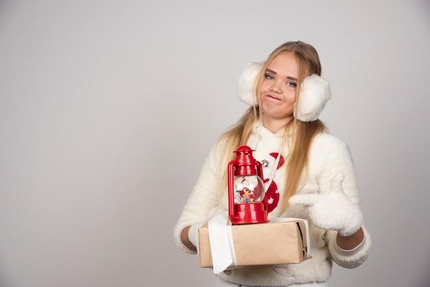 Jeune femme en tenue blanche pointant sur cadeau de noël.
