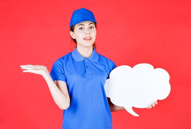 Jeune femme en tenue bleue tenant une bulle de dialogue vide sur le rouge.
