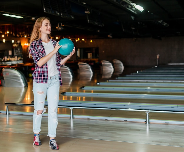Jeune femme, tenue, boule bowling, long shot