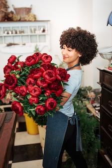Jeune femme, tenue, bouquet fleurs rouges, dans, magasin