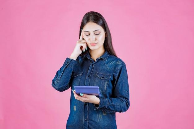 Jeune femme, tenue, a, calculatrice bleue, et, pensée