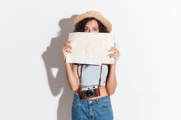 Jeune, femme, tenue, carte, regarder, appareil photo, isolé