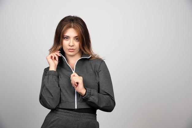 Jeune femme en tenue décontractée debout et posant.