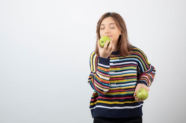 Jeune femme en tenue décontractée, manger une pomme verte sur fond blanc.