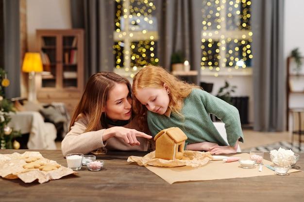 Jeune femme en tenue décontractée pointant sur maison en pain d'épice fait maison tout en discutant avec sa mignonne petite fille qui y vit