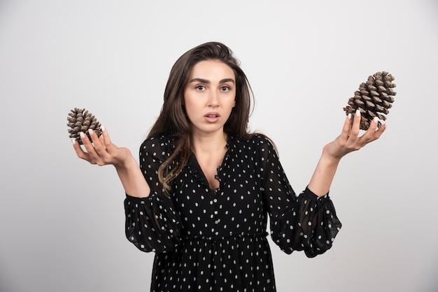Jeune femme, tenue, deux grosses pommes de pin