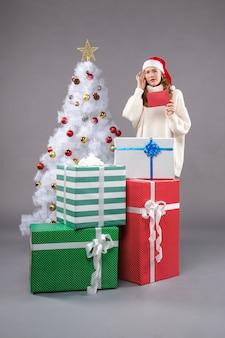 Jeune femme, tenue, enveloppe, sur, plancher gris, vacances, nouvel an, noël