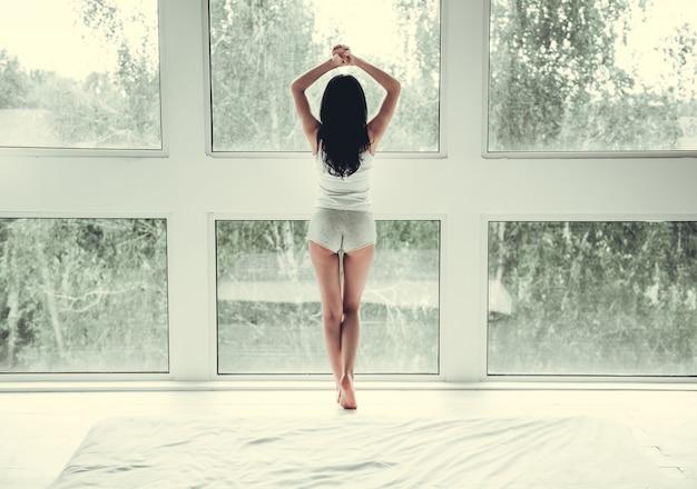 Jeune femme en tenue de maison debout sur ses orteils.