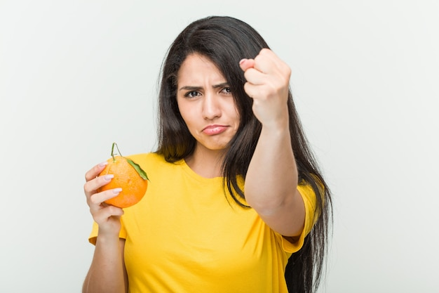 Jeune femme, tenue, orange, poing projection
