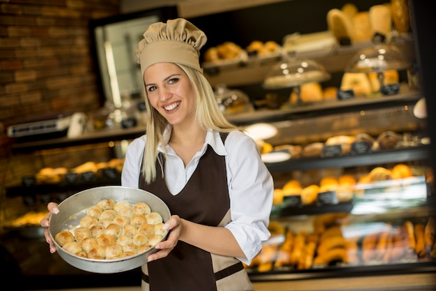Jeune femme, tenue, panier, pâtisserie, boulangerie, sourire joyeuse, appareil photo