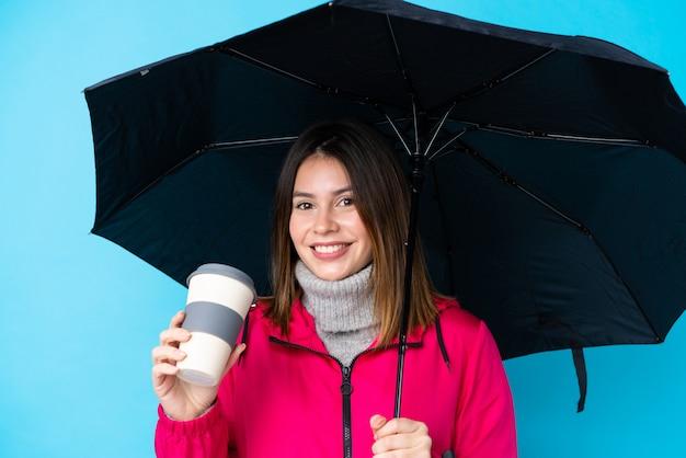 Jeune, femme, tenue, parapluie, café, emporter, bleu, mur