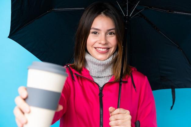Jeune, femme, tenue, parapluie, café, emporter, isolé, bleu, mur