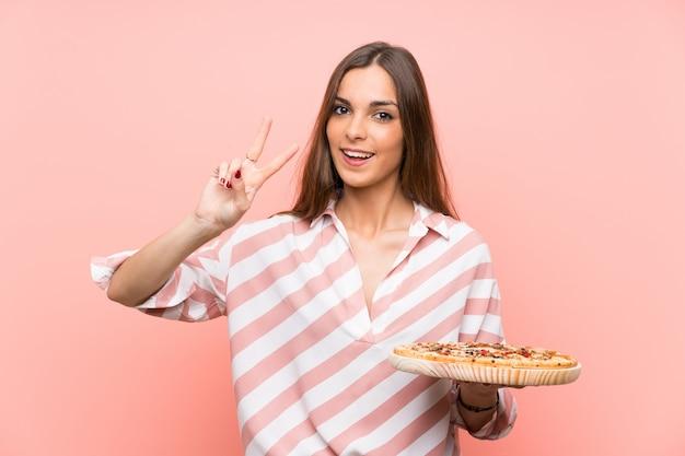 Jeune femme, tenue, pizza, sourire, projection, signe victoire