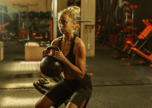 Jeune femme en tenue de sport faisant de l'exercice avec kettlebell dans la salle de gym. concept de mode de vie sain. entraînement du corps avec des poids libres. entraînement fonctionnel